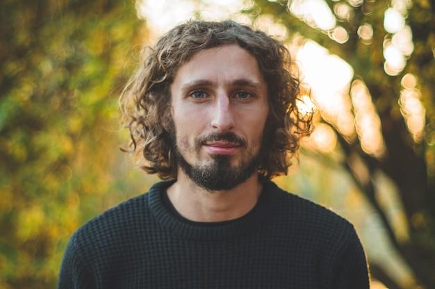 Ritratto di un bel ragazzo dai capelli ricci sulla natura Foto Premium