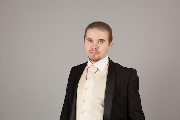 Ritratto di bel giovane in smoking. abbigliamento alla moda per la serata festiva sul muro grigio con copyspace Foto Premium