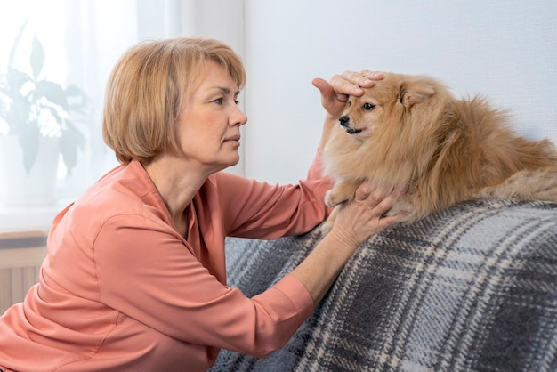 Ritratto di felice bella donna con il suo animale domestico a casa, anziana signora senior sta accarezzando pomerania Foto Premium
