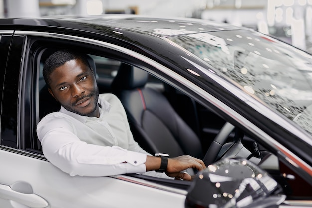 Ritratto di uomo d'affari nero felice all'interno di auto di lusso Foto Premium