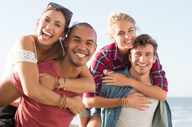 Ritratto di felice e allegro giovani coppie sulle spalle divertendosi Foto Premium