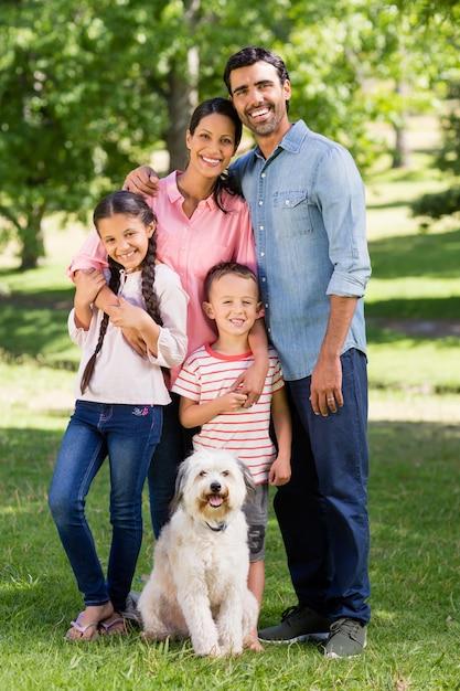 Ritratto della famiglia felice con il loro cane che sta nel parco Foto Premium
