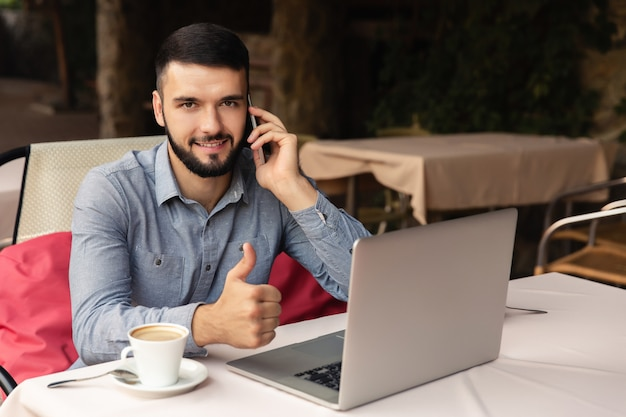 Ritratto di uomo felice che lavora da casa, si siede con una tazza di caffè al tavolo, parlando con un telefono intelligente Foto Premium