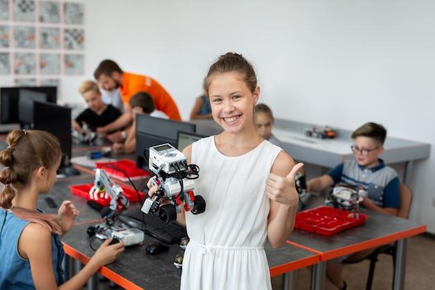 Ritratto di una ragazza studentessa felice in una classe di robotica, tiene un robot assemblato da parti in plastica programmate su un computer Foto Premium