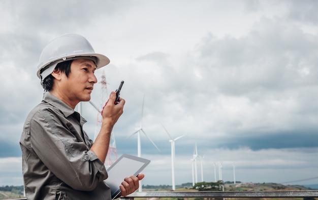 Immagini ritratto di un ingegnere asiatico, tecnico uomo in piedi, tenendo in mano un tablet e utilizzando la comunicazione radio, con turbine eoliche, alle persone e al concetto di produzione di elettricità. Foto Premium