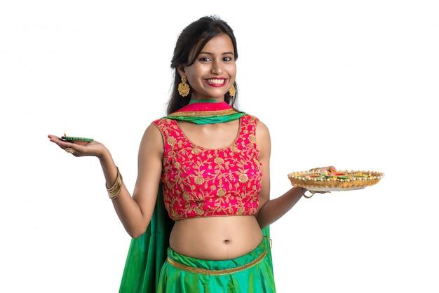 Ritratto di una ragazza tradizionale indiana che tiene diya e celebra diwali o deepavali Foto Premium