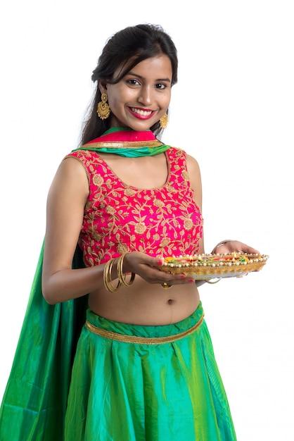 Ritratto di una ragazza indiana tradizionale con diya, ragazza che celebra diwali o deepavali con in mano una lampada a olio durante il festival di luce sulla superficie bianca Foto Premium