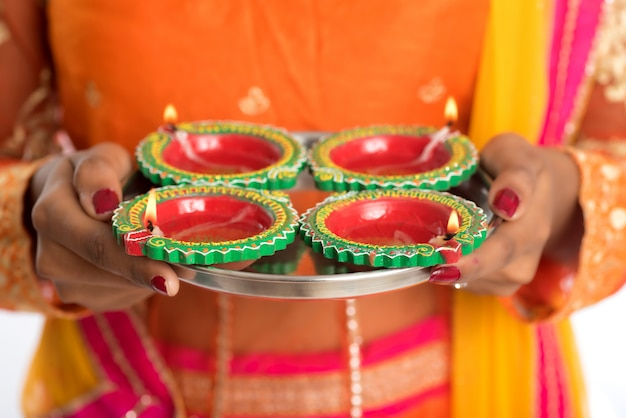 Ritratto di una ragazza indiana tradizionale in possesso di diya, ragazza che celebra diwali o deepavali con azienda lampada ad olio durante il festival della luce sul muro bianco Foto Premium