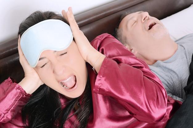 Ritratto della donna irritata che blocca le orecchie con le mani mentre uomo che russa sul letto Foto Premium