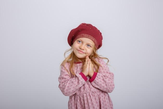 Ritratto di piccola ragazza bionda in berretto che chiede speranza isolata su fondo bianco Foto Premium