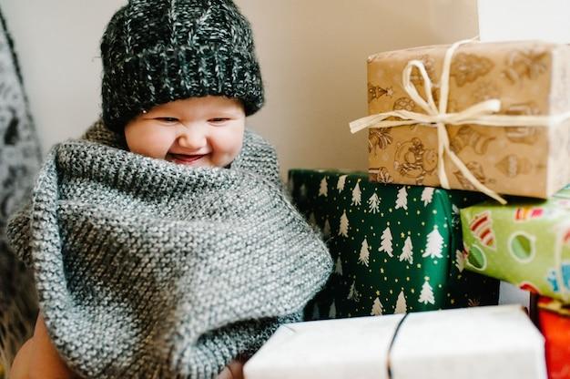 Ritratto di una bambina in un caldo cappello lavorato a maglia con una sciarpa, si siede nella stanza con doni. concetto di compleanno festivo. bambino nella foto. neonato. festa della donna. buon natale, buone vacanze. Foto Premium