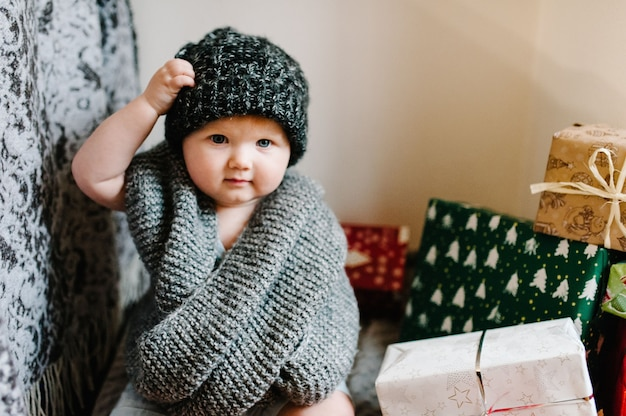 Ritratto di una bambina in una calda sciarpa lavorata a maglia, rimuove il cappello, si siede nella stanza con i regali. concetto di compleanno festivo. bambino nella foto. neonato. festa della donna. buon natale, buone vacanze. Foto Premium