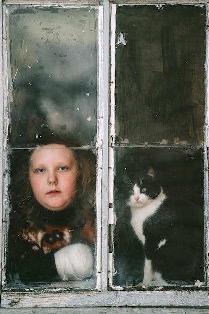 Ritratto di piccola ragazza isolata di auto con la faccia noiosa e il suo adorabile gattino Foto Premium