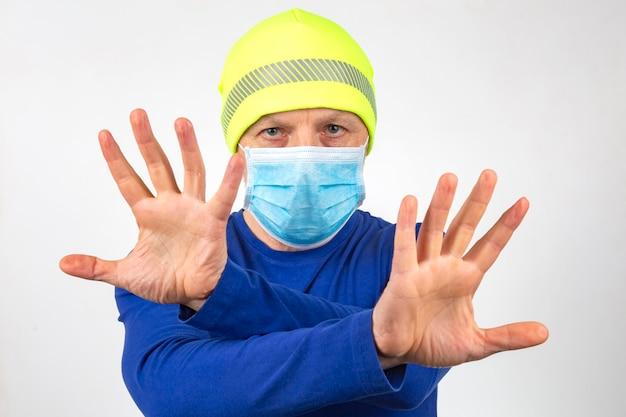 Ritratto di un uomo in una mascherina medica con le mani alzate. mani pulite e quarantena Foto Premium