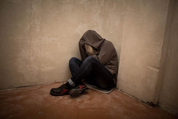 Ritratto di uomo triste, tossicodipendente uomo seduto sul pavimento nell'angolo Foto Premium