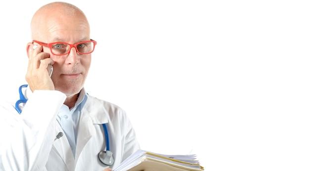 Ritratto di medico maturo con telefono isolato Foto Premium