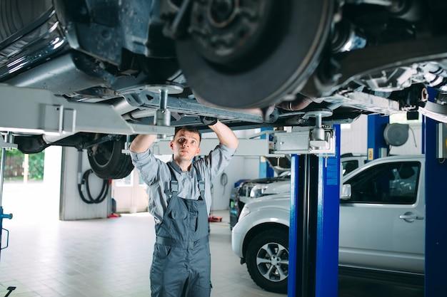 Ritratto di un meccanico che ripara un'auto sollevata. Foto Premium