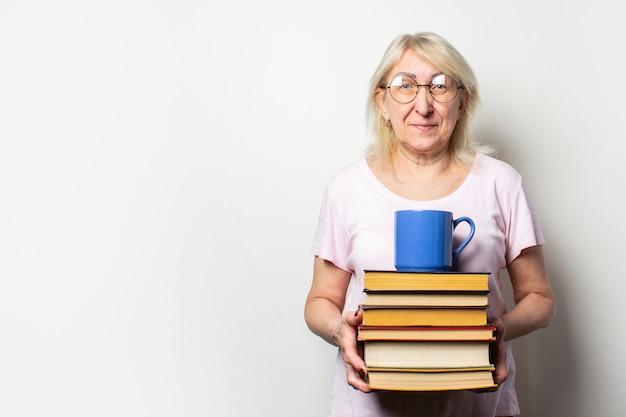 Il ritratto di una donna anziana amichevole con un sorriso in una maglietta e gli occhiali casuali tiene una pila di libri e una tazza su una parete leggera isolata. volto emotivo. concept book club, tempo libero, educazione Foto Premium