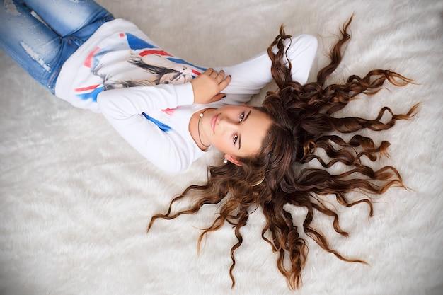 Ritratto di una bella ragazza adolescente sdraiato sul pavimento con i suoi lunghi capelli ondulati Foto Premium