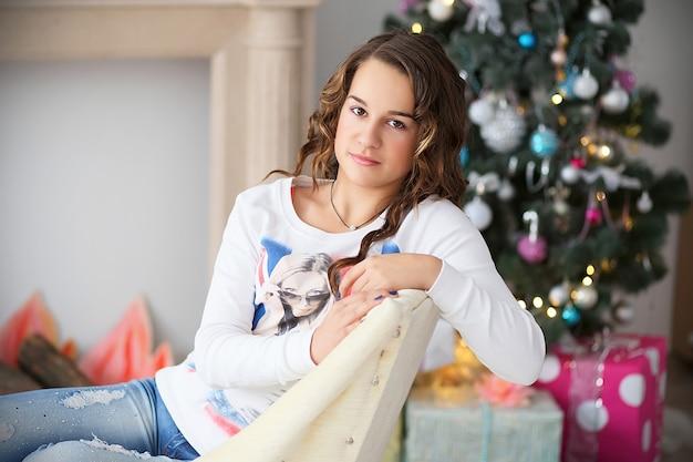 Ritratto di una bella ragazza adolescente con capelli lunghi fluenti in interni con decorazioni natalizie Foto Premium