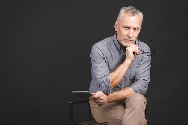 Ritratto di uomo anziano pensionato con in mano una tavoletta digitale mentre era seduto, tenendo gli occhiali. Foto Premium