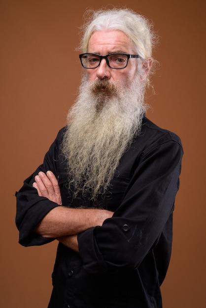 Ritratto di uomo barbuto anziano su colore marrone Foto Premium