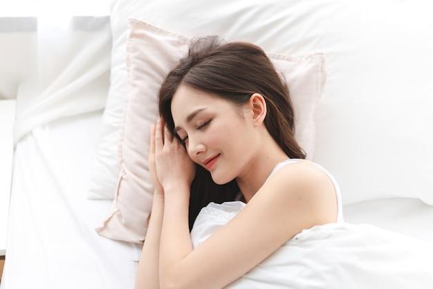 Il ritratto di giovane donna addormentata dell'asia gode e si rilassa la menzogne sul letto con gli occhi vicini in camera da letto a casa bellezza asiatica Foto Premium