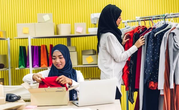 Ritratto di sorridente bella due musulmani proprietario donna asiatica libero professionista pmi business shopping online lavorando su un computer portatile con cassetta dei pacchi sul tavolo a casa - business online spedizione e consegna Foto Premium