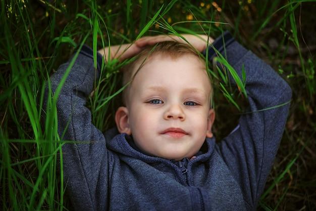 Ritratto di un ragazzino biondo sorridente sdraiato sull'erba verde Foto Premium