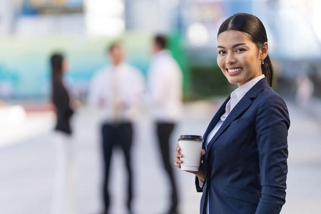 Ritratto della donna sorridente di affari che tiene una tazza di caffè mentre levandosi in piedi davanti agli edifici per uffici moderni Foto Premium