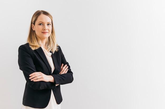 Ritratto di sorridente fiduciosa giovane imprenditrice con braccio attraversato Foto Premium