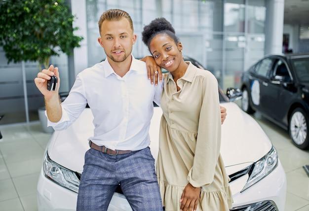 Ritratto della coppia sposata sorridente con le chiavi dalla loro nuova automobile Foto Premium