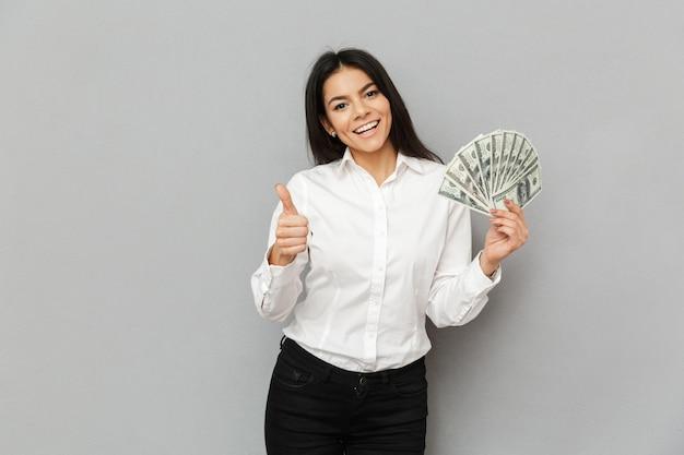 Ritratto di donna castana di successo che indossa abito formale che tiene un sacco di dollari in mano e che mostra il pollice in su, isolato sopra il muro grigio Foto Premium