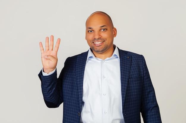 Ritratto di un giovane uomo d'affari afroamericano di successo, mostrando con le dita al numero quattro, sorridente, fiducioso e felice. l'uomo mostra quattro dita. numero 4. Foto Premium