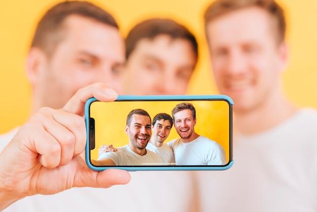 Un ritratto di un amico di tre maschi che prende selfie sullo smartphone Foto Premium