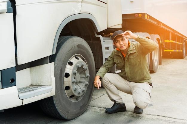 Ritratto dell'autista di camion che ispeziona sicurezza le ruote del camion Foto Premium