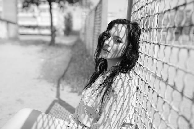 Ritratto di donna in una striscia d'ombra all'aperto nel parco estivo Foto Premium