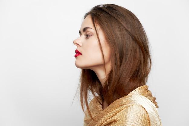 Un ritratto di una donna con una sciarpa guarda da parte trucco labbra rosse isolato Foto Premium