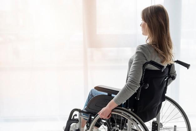 Ritratto delle donne nel distogliere lo sguardo della sedia a rotelle Foto Premium