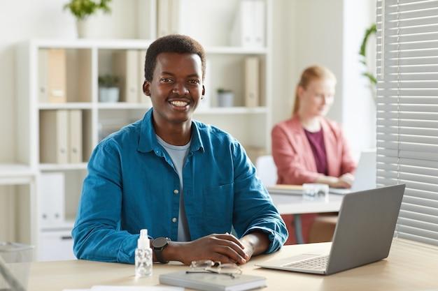 Ritratto di giovane uomo afro-americano sorridente che lavora alla scrivania in ufficio con i colleghi Foto Premium