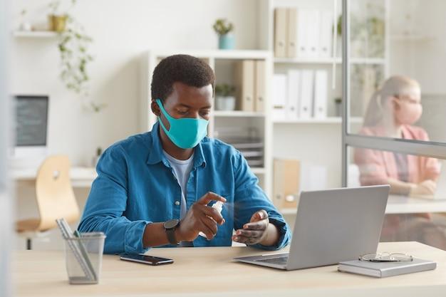 Ritratto di giovane uomo afro-americano che indossa la maschera igienizzante mani mentre è seduto alla scrivania in cabina all'ufficio post pandemia Foto Premium