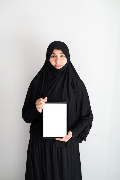 Ritratto di giovane donna asiatica che indossa l'hijab, lavorando a casa con tablet Foto Premium