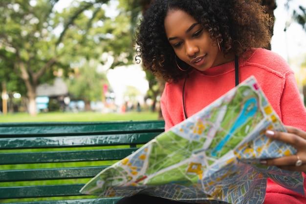 Ritratto di giovane bella donna afroamericana seduta su una panchina nel parco e guardando una mappa. concetto di viaggio. all'aperto. Foto Premium