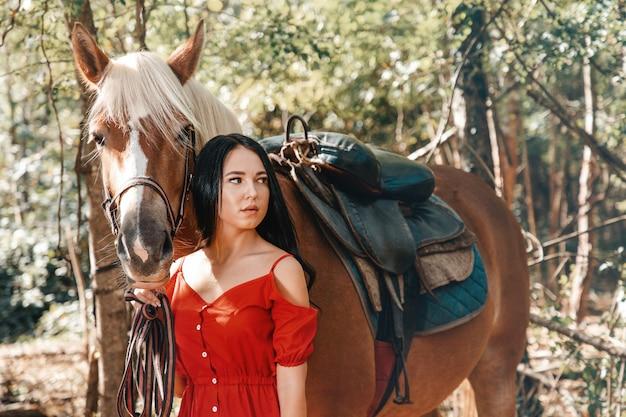 Ritratto di una giovane bella donna castana che tiene un cavallo per la briglia Foto Premium