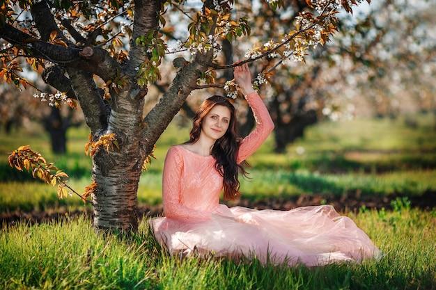 Ritratto di una giovane bella ragazza nel frutteto di primavera Foto Premium