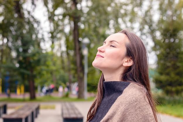 Ritratto di giovane bella donna che fa respiro dell'aria fresca di autunno in un parco verde. Foto Premium