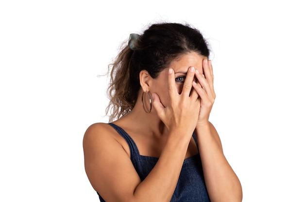 Ritratto di giovane bella donna in cerca timido nascondersi dietro la mano e sorridente in studio su sfondo bianco. Foto Premium