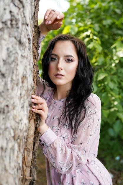 Ritratto di giovane bella donna vicino all'albero Foto Premium