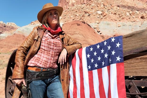 Ritratto di una giovane cowgirl bionda con la bandiera americana Foto Premium