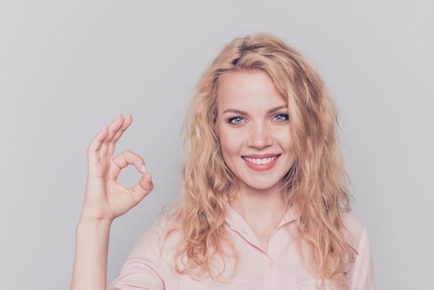 Ritratto di giovane donna sorridente bionda che mostra ok-segno su grigio Foto Premium